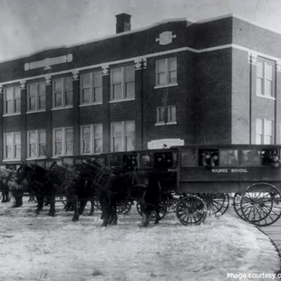Horse drawn school buses sit in front of the Waukee School in 1917.